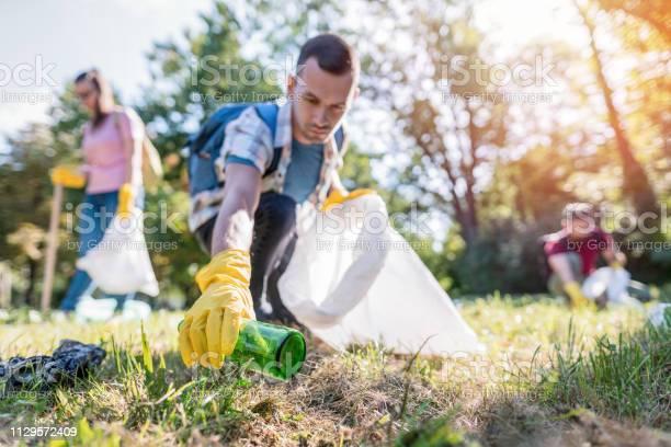 生徒達がゴミ箱から地元の公園を掃除 - 20-24歳のストックフォトや画像を多数ご用意