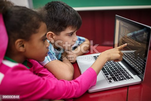 Students creating programs while using laptop. Boy and girl learning coding in school. They are at desk in classroom.