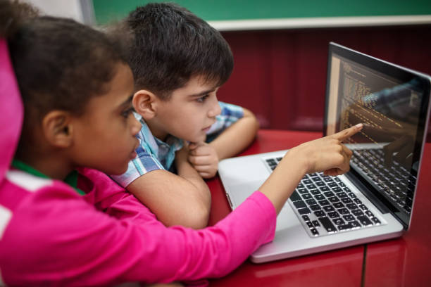 Students creating programs while using laptop Students creating programs while using laptop. Boy and girl learning coding in school. They are at desk in classroom. coding stock pictures, royalty-free photos & images