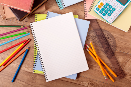 Student's desk with open notebook, text books, various pencils and calculator.  Alternative version shown below: