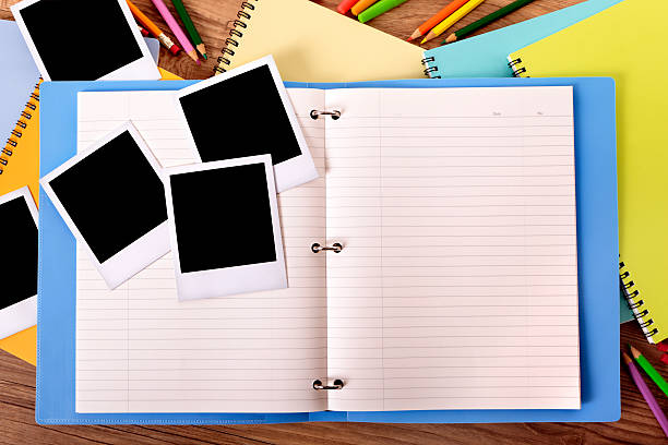 Student's desk with blue project folder and blank photos. stock photo