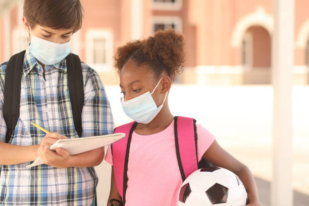 Students do homework on school campus. Masks for COVID-19. Back to school. Latin and African descent friends on school campus. They both wear a masks for COVID-19, Coronavirus protection.  They do homework together.  School in background. covid-19 stock pictures, royalty-free photos & images