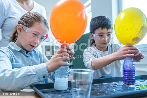 Students doing self inflating balloon science experiment in laboratory.