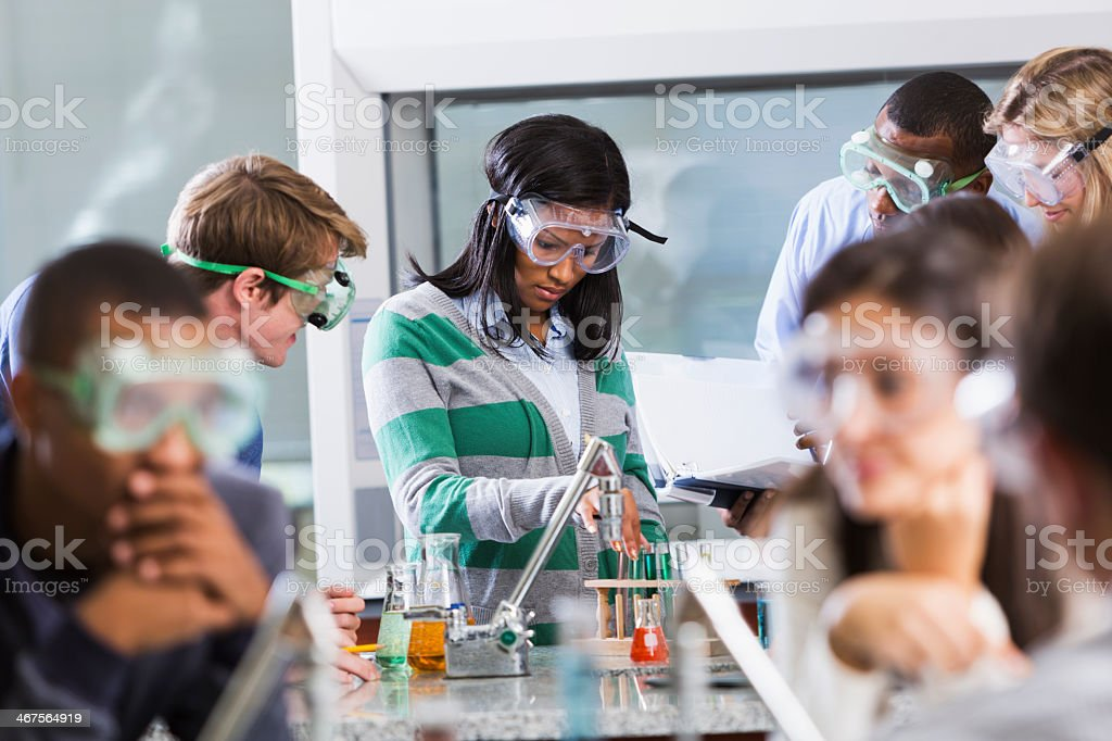 Students doing experiment in chemistry class stock photo