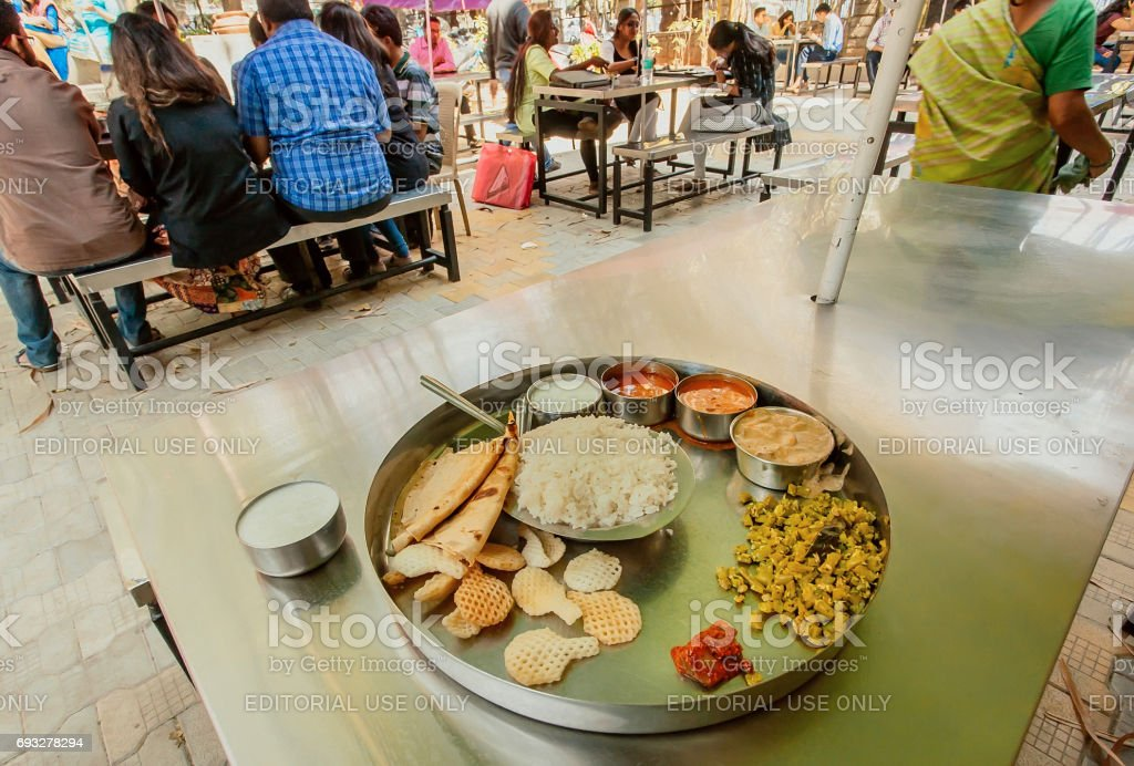 Students eating indian vegeterian food thali in outdoor cafe stock photo