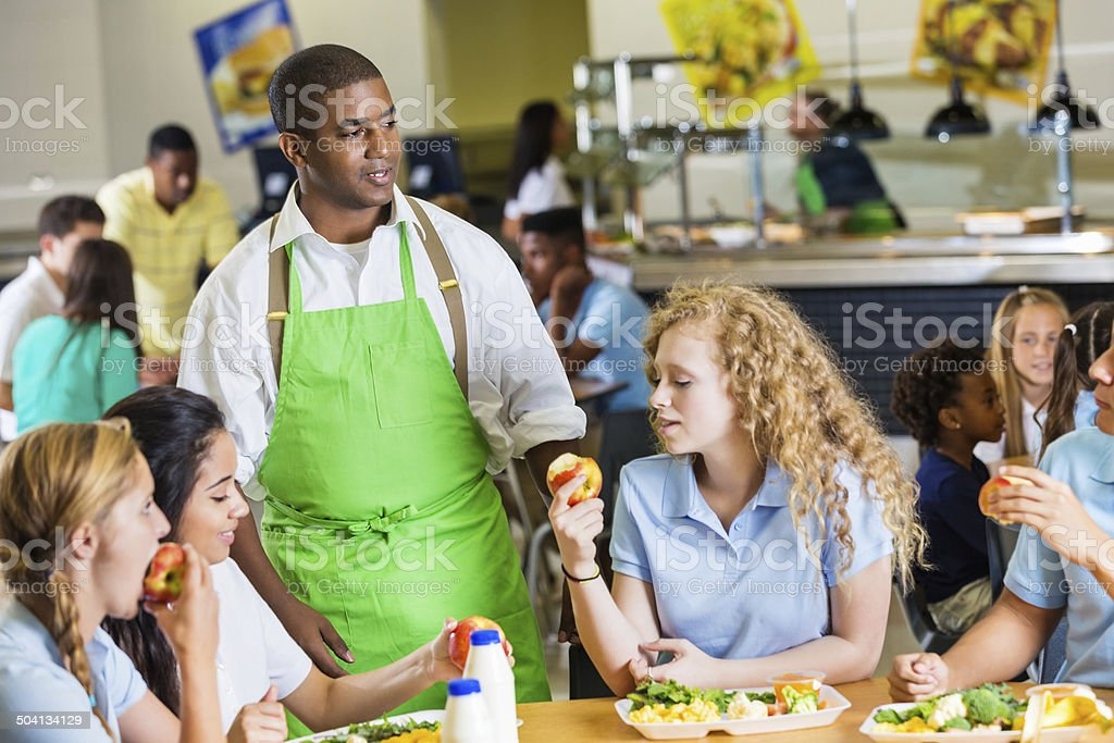 Students enjoy apples and chat during school lunch break stock photo