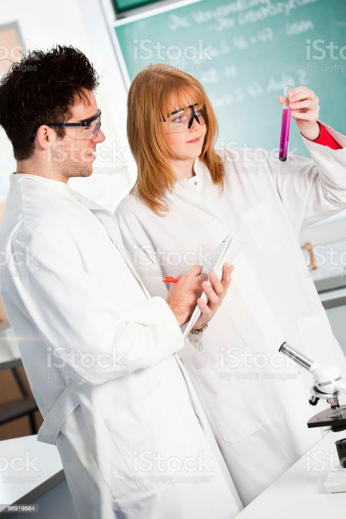 Students examining a test tube and taking notes royalty-free stock photo