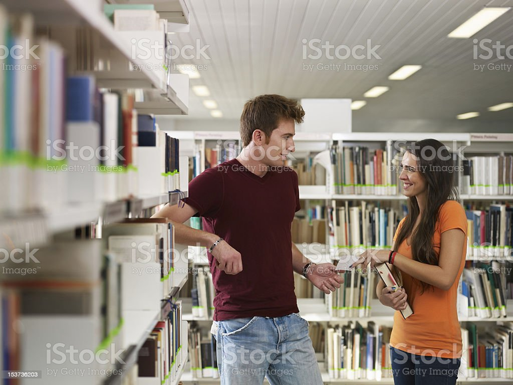 students flirting in library stock photo