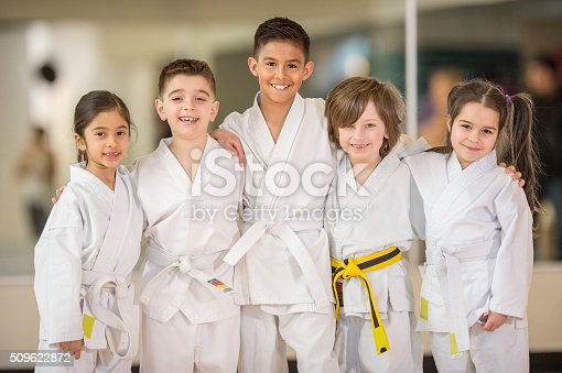 A multi-ethnic group of elementary age children are standing in a row together before their karate class. They are all smiling while looking at the camera.
