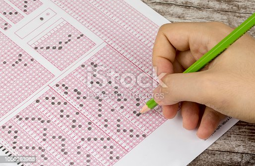 Students hand doing exams quiz test paper with pencil drawing selected choice on answer sheets at school