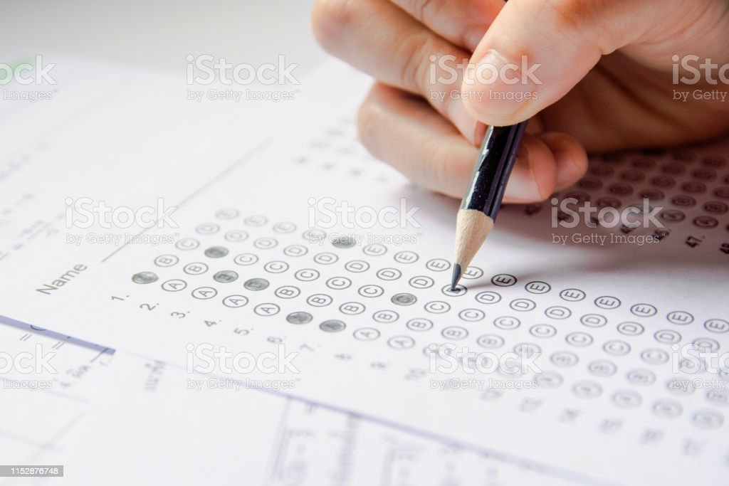 Students hand holding pencil writing selected choice on answer sheets...