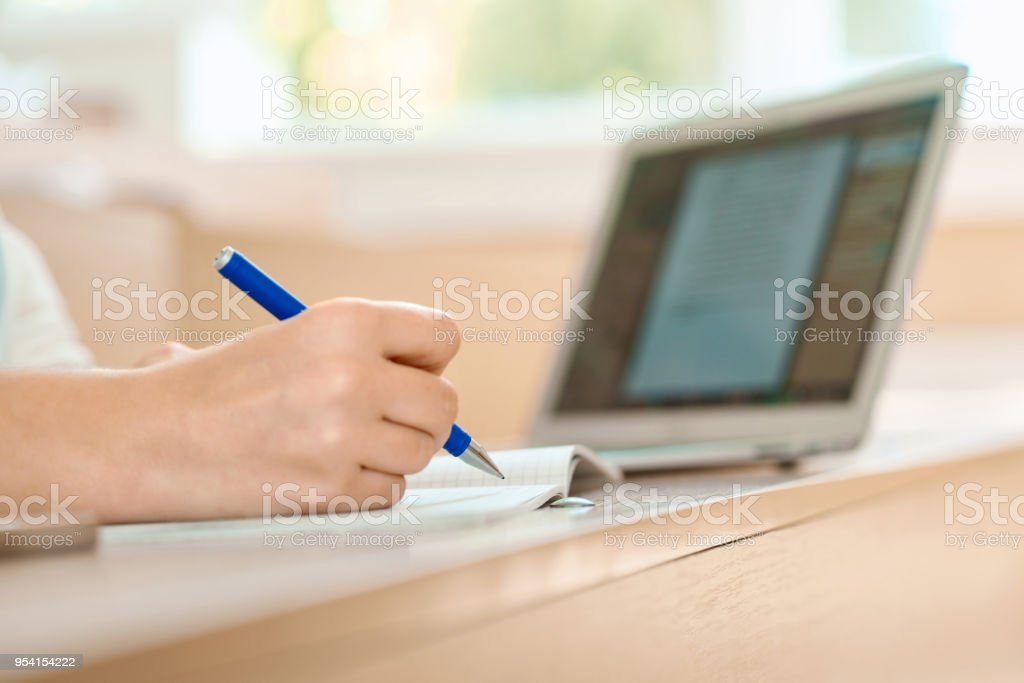 Student's hand keeping a pen and writing in notebook. stock photo