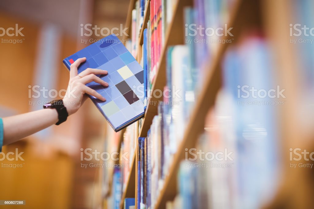 Students hand with smartwatch picking book from bookshelf royalty-free stock photo