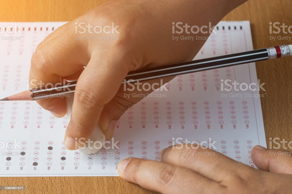 https www istockphoto com photo students hands holding black pencil using erase delete answer test on wood table in gm1080067572 289479922