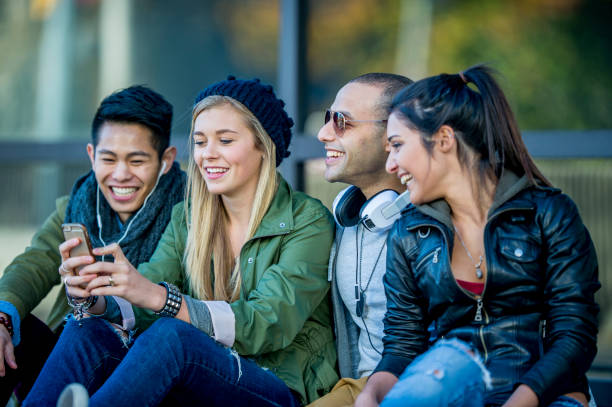 Students Hanging Out A multi-ethnic group of young adults are sitting in a public area outside. One woman is looking at her smartphone, and is getting ready to take a selfie of the group. generation z stock pictures, royalty-free photos & images