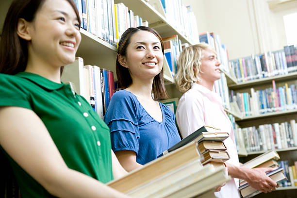 Students holding book in library stock photo