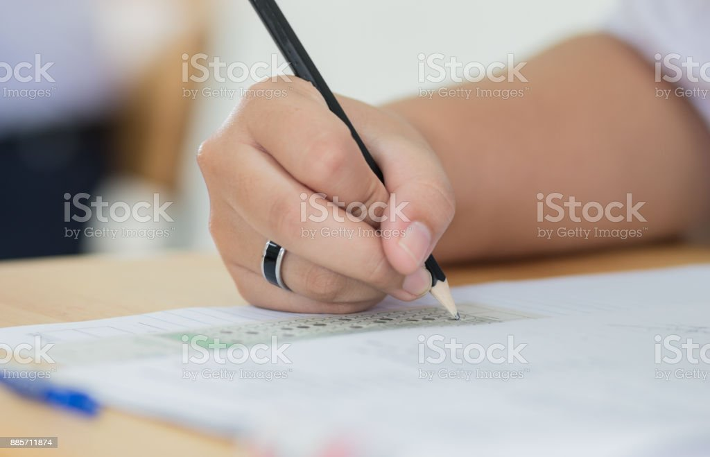 Students holding pen in hands taking exams, writing examination room...