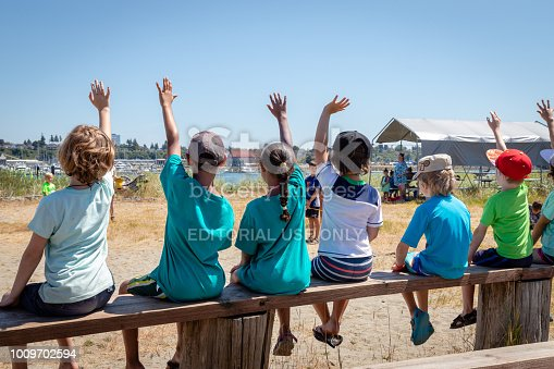 istock Students holding their hands up to volunter or ask questions of their teacher at an outdoor nature class. 1009702594