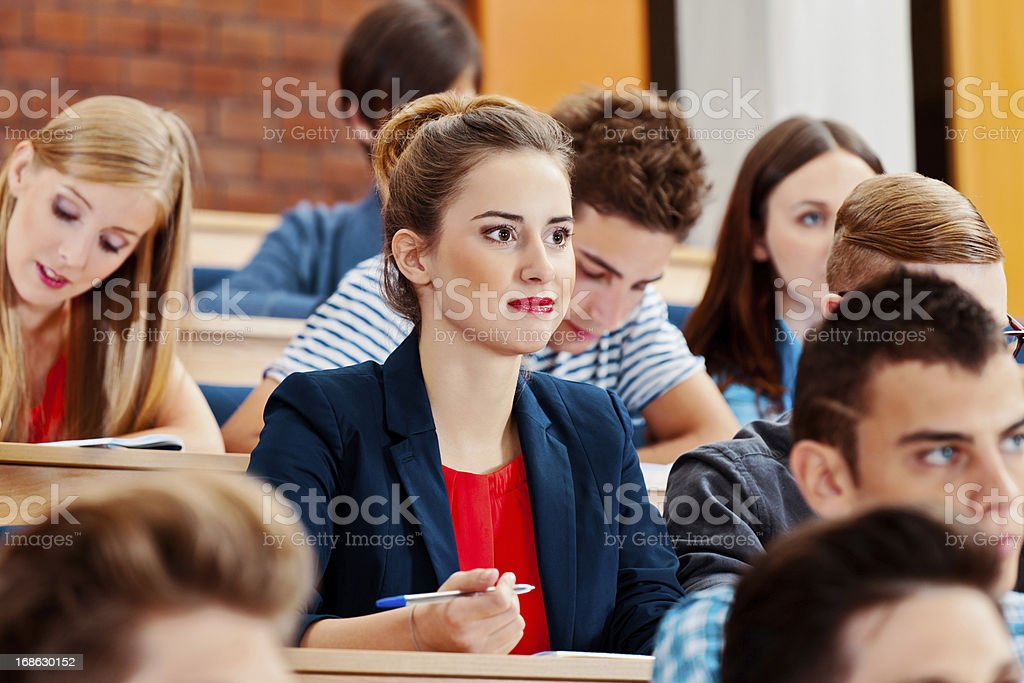 Students in a lecture hall Group of high school students sitting in the lecture hall at university and writting test. 20-24 Years Stock Photo