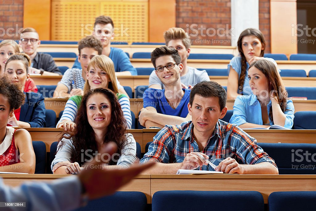 Students in a lecture hall Large group of students sitting in the lecture hall at university and listening to their teacher.  20-24 Years Stock Photo
