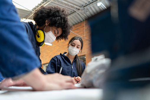 Students in a manufacturing class at school wearing facemasks during the COVID-19 pandemic - education concepts