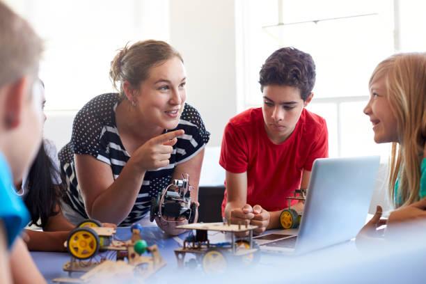 estudantes em depois da escola de programação de computador classe de construção e aprendizagem para programar robô veículo - professor - fotografias e filmes do acervo