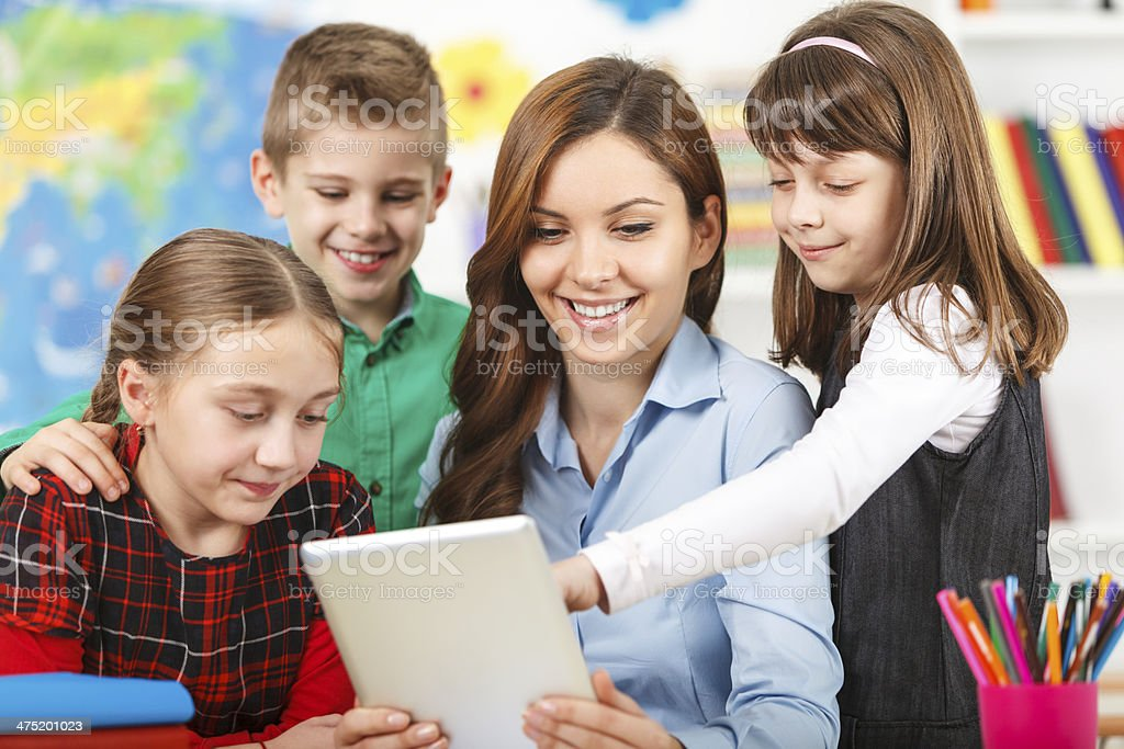Students In Classroom Using Digital Tablet With Teacher royalty-free stock photo