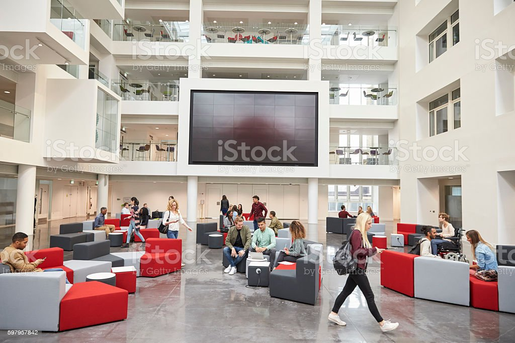 Students in front of screen in atrium of modern university stock photo