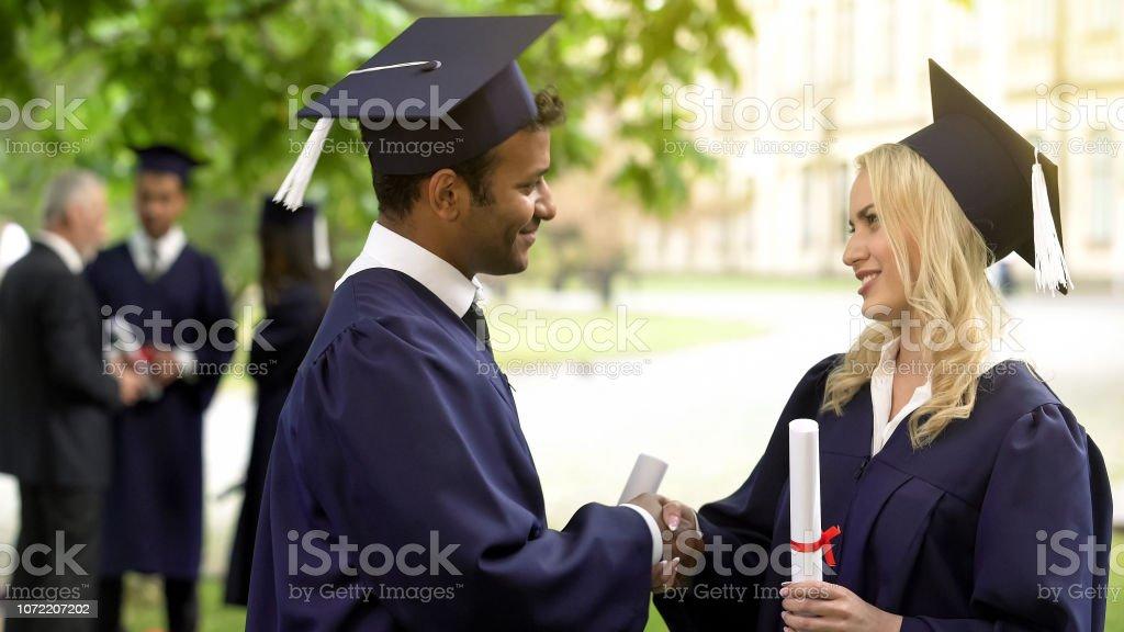 4e5597f00 Estudiantes De Vestido De Graduación Con Diplomas Hablar Agitando ...