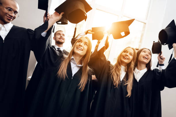 Students in mantles are happy that they finish their studies at the university. Students in mantles are happy that they finish their studies at the university. They are university graduates. They are very happy about this. alumnus stock pictures, royalty-free photos & images