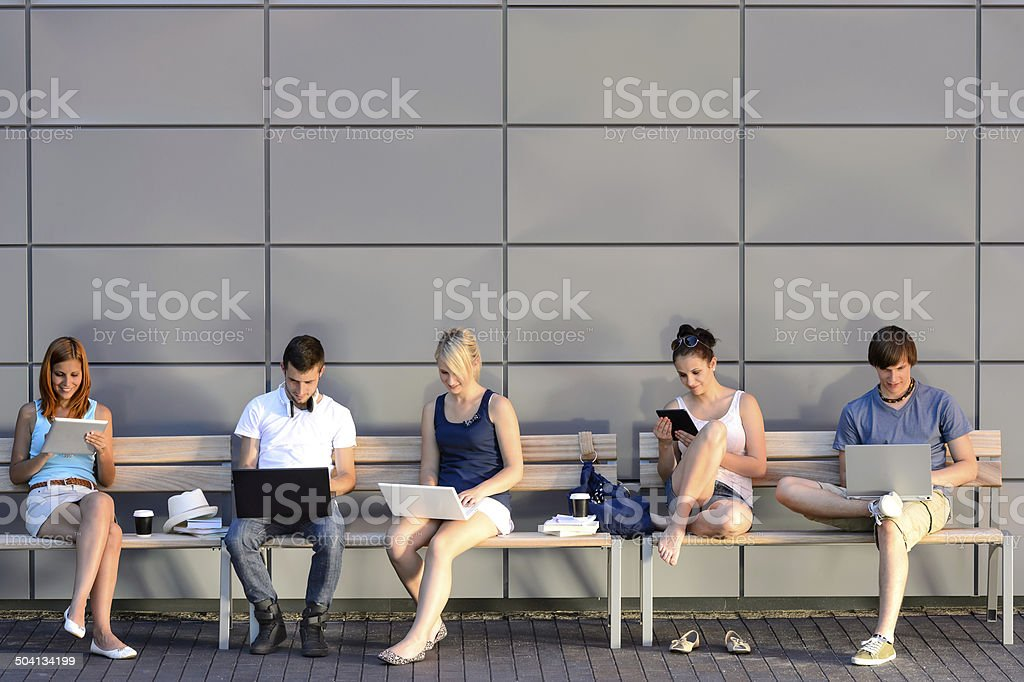 Students internet computer addiction sitting bench stock photo