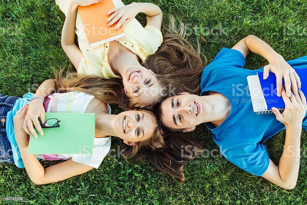 Students laying on a meadow stock photo