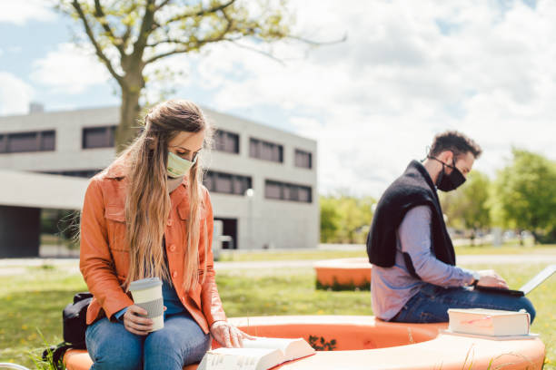 Students learning on campus keeping social distance stock photo