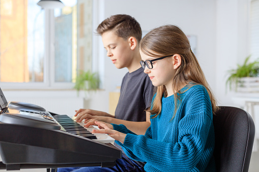 Students Learning Piano In Training Class Stock Photo - Download Image Now
