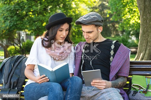 Two happy students learning together on line with a tablet and a textbook sitting in a park