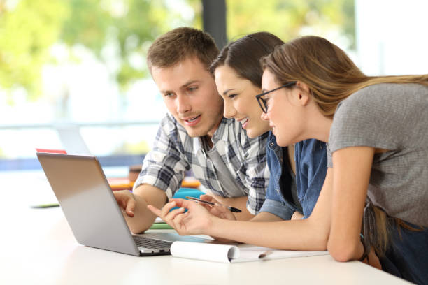 Students learning together on line in a classroom stock photo