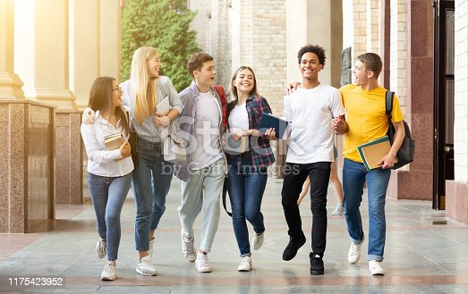 istock Students life. Friends walking in university campus 1175423952