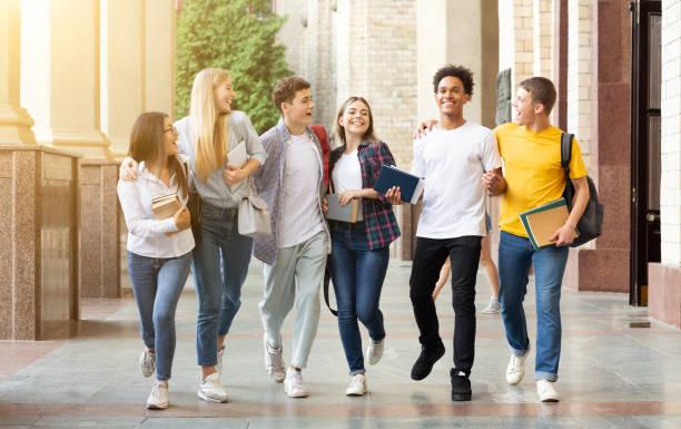 students life. friends walking in university campus - compagni scuola foto e immagini stock