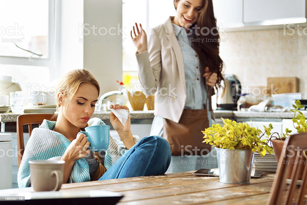 Students lifestyle Young woman has a cold, sitting in a kitchen wrapped in blanket, holding teacup and handkerchief, with her roommate going out and saying goodbye. 20-24 Years Stock Photo