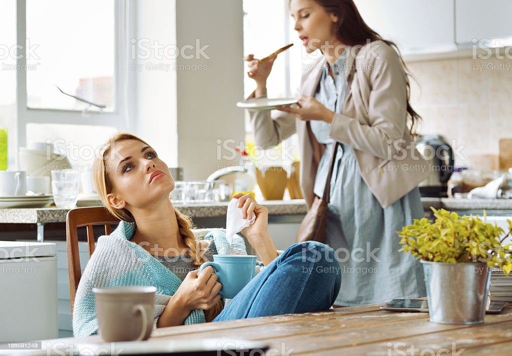Students lifestyle Young woman has a cold, sitting in a kitchen wrapped in blanket, holding teacup and handkerchief, with her friend standing in the background and eating breakfast. 20-24 Years Stock Photo