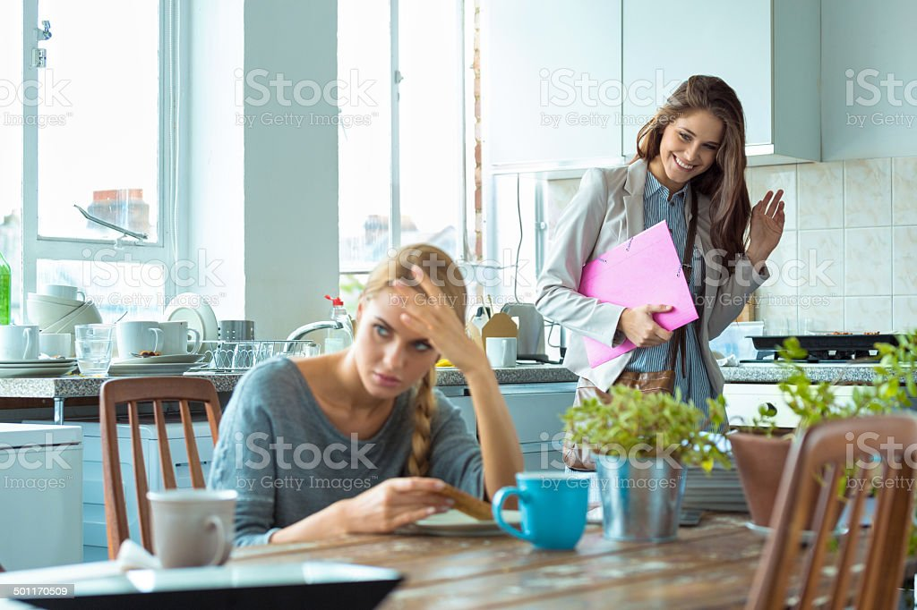 Students lifestyle Worried young woman eating breakfast in the kitchen while her friend going out. 20-24 Years Stock Photo
