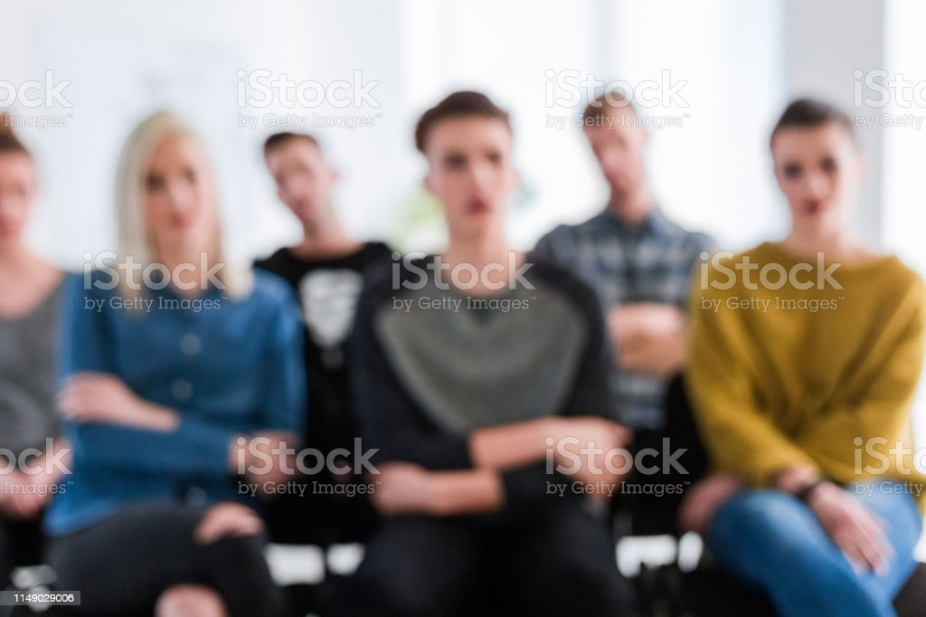 Students listening during therapy session Men and women attending therapy session. Defocused image of university students are sitting together. They are listening while concentrating. 18-19 Years Stock Photo