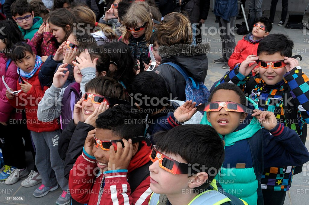 students looking at the solar eclipse stock photo