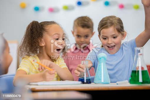 istock Students make surprised faces in science class while doing chemistry experiment 1159500479