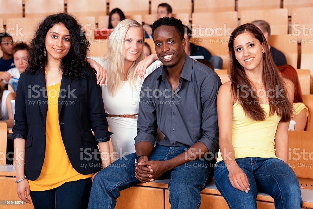 smiling students of different ethnicity in auditorium