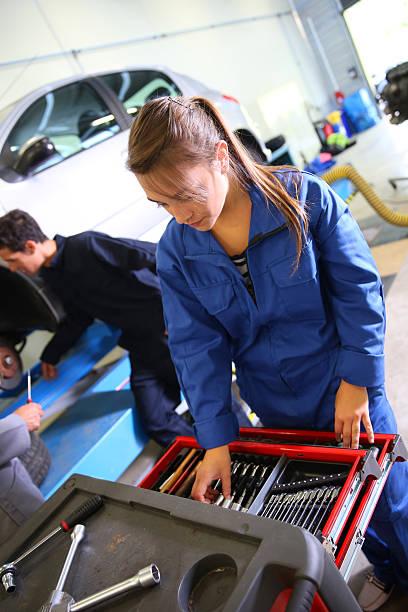 Students of mechanics working in garage stock photo