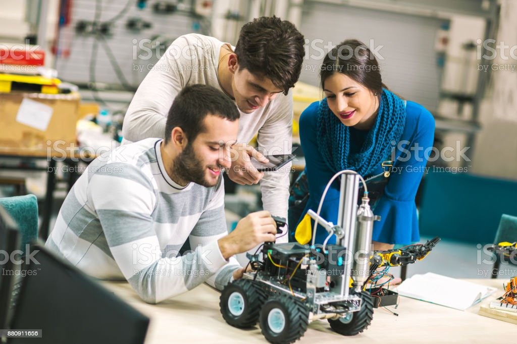 Students of robotics preparing robot for testing stock photo