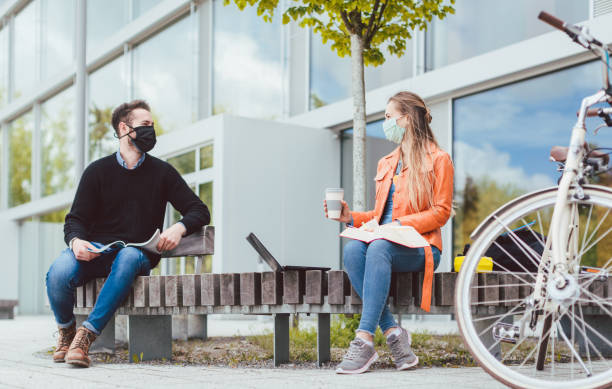 Students on university campus keeping social distance due to coronavirus stock photo