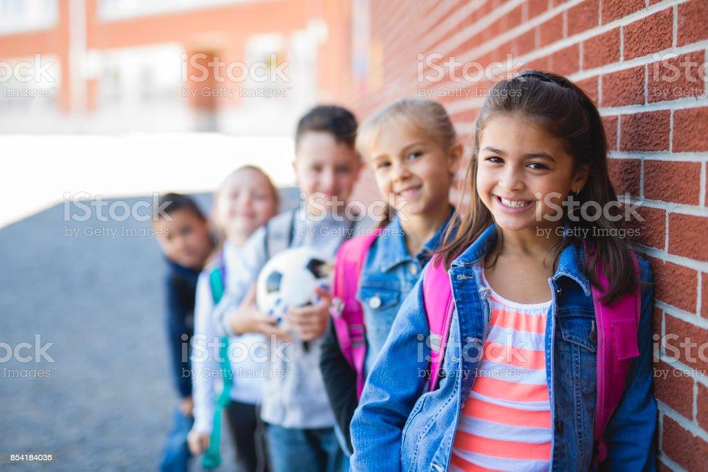 estudiantes fuera de la escuela de pie juntos - foto de stock