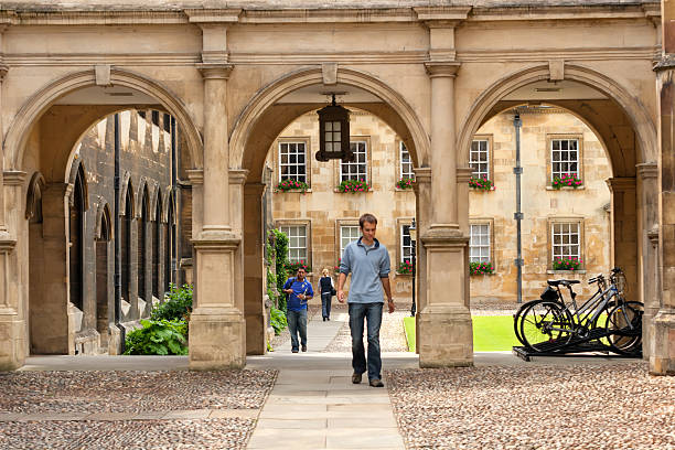 students passing through a college campus gate in cambridge university - cambridge university stock photos and pictures